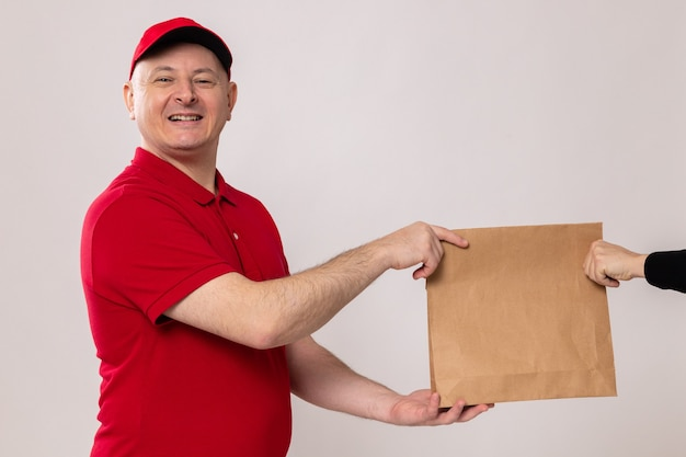 Felice e positivo fattorino in uniforme rossa e berretto che dà un pacchetto di carta al cliente sorridente amichevole