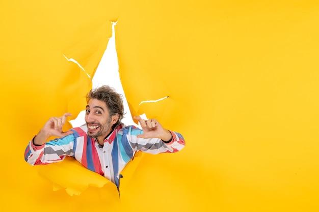 Felice ragazzo barbuto positivo ed emotivo in un buco strappato e sfondo libero in carta gialla