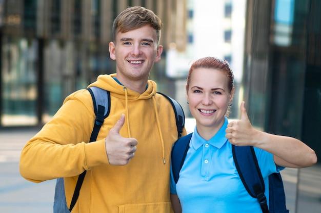 幸せな肯定的なヨーロッパの若いカップル、友人、大学や大学の成功した学生のバックパックを屋外のキャンパスで一緒に笑っています。
