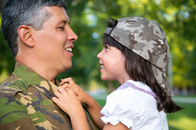 행복 한 긍정적 인 아버지 팔에 작은 딸을 들고, 소녀를 포옹 하 고 군사 임무 여행에서 돌아온 후 야외에서 그녀와 이야기. 근접 촬영. 가족 상봉 또는 귀국 개념