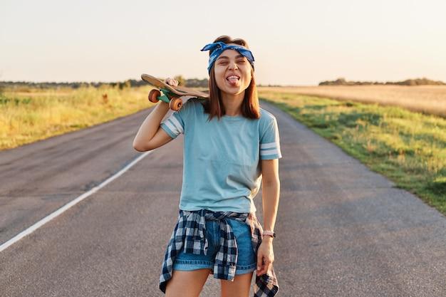 Tシャツを着て、肩にスケートボードを持った短いヘアバンドを着て、面白い表情、しかめっ面、舌を見せてカメラを直接見ている幸せなポジティブな女性。