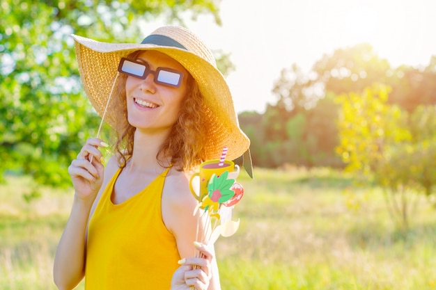 Happy positive fun smiling girl woman wear yellow dress straw hat paper glasses holds in hand colorful photo props mustaches lips on summer spring sunny green light field. photoshoot party concept.
