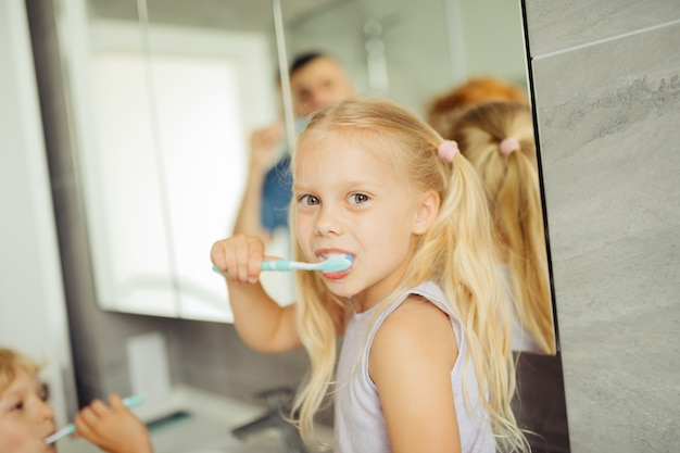 歯ブラシを持って幸せな肯定的な女の子