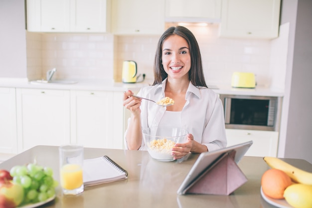 Happy positive girl is smiling. she holds a spoon with milk and corn flakes.