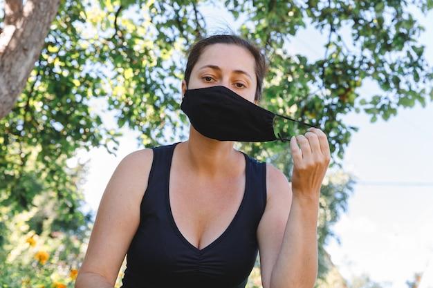 행복한 긍정적인 소녀는 야외에서 얼굴에서 보호 의료 마스크를 벗습니다. 예방 접종 후 웃는 마스크를 제거 하는 젊은 여자. 코로나바이러스 전염병 코비드 19 개념. 봄꽃 꽃가루 알레르기.