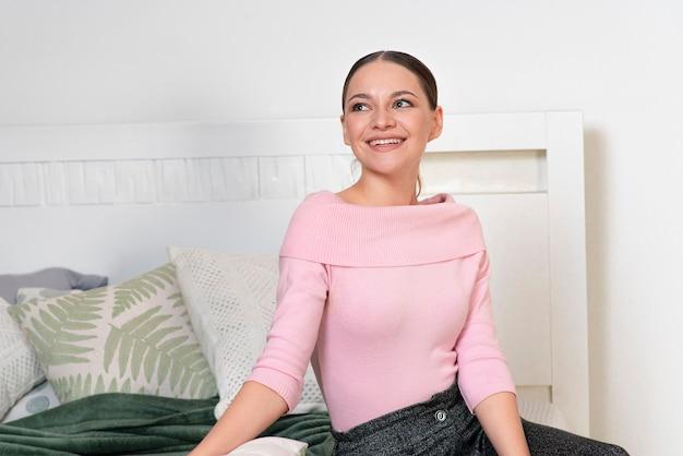 행복 한 긍정적 인 소녀 쾌활 한 젊은 여자 침실 휴식에 베개와 함께 침대에 앉아