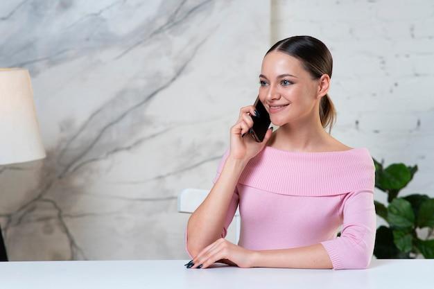 Счастливая позитивная девушка, молодая довольно красивая женщина разговаривает по мобильному телефону, используя смартфон