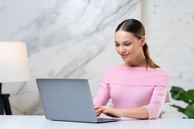 행복 한 긍정적 인 소녀, 젊은 여자 프리랜서는 그녀의 노트북 컴퓨터에서 작업
