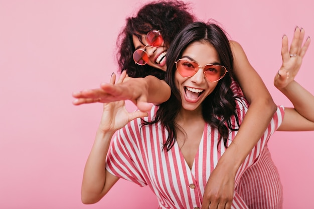 Счастливые, позитивные девушки в светло-розовой летней одежде позируют с искренней улыбкой. портрет африканских моделей