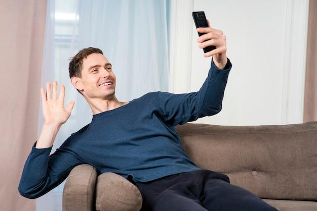 Счастливый позитивный парень, молодой расслабленный красивый мужчина разговаривает, смотрит на его мобильный телефон, смартфон
