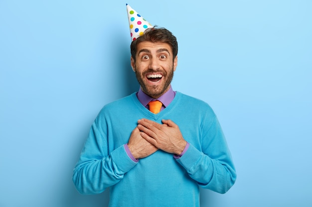 幸せなポジティブハンサムな誕生日の男は感謝と感動を感じます