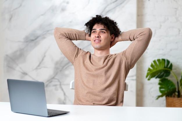 행복 긍정적 인 잘 생긴 즐거운 남자 젊은 성공적인 남자는 자신의 노트북에서 작업을 마친 후 쉬고있다