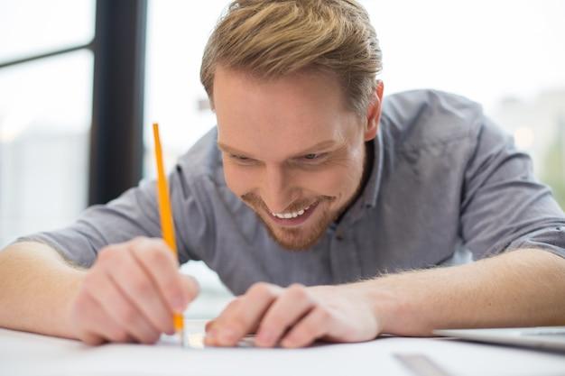 연필을 들고 새로운 아이디어를 가지고 메모를하는 행복 긍정적 인 잘 생긴 남자