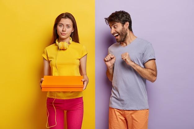 Счастливый позитивный мужчина интригует взглядом на коробку с подарком, хочет заглянуть внутрь, серьезная женщина в желтой футболке несет пакет