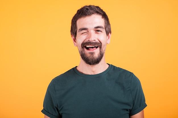 カメラを見て、黄色の背景で隔離のまばたき幸せなポジティブな男