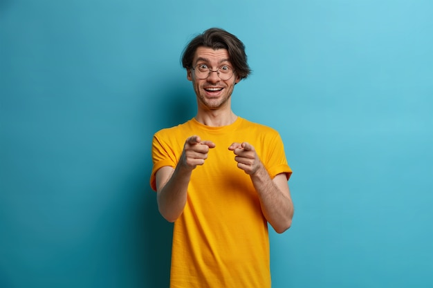 Happy positive man points fingers at you, picks someone, has cheerful expression, says well done, praises friend for good work or awesome result, dressed casually, isolated on blue wall