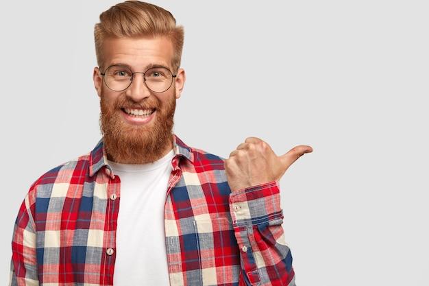 長く厚い生姜ひげと口ひげを持つ幸せなポジティブな男は、市松模様のシャツを着て、フレンドリーな笑顔を持っています