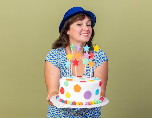 Happy and positive middle age woman in party hat holding birthday cake  smiling cheerfully celebrating birthday party standing over green wall