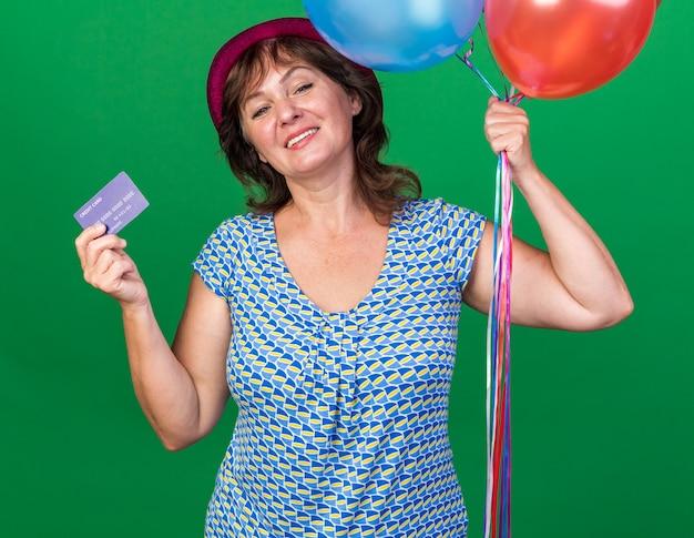 Felice e positiva donna di mezza età con cappello da festa in possesso di palloncini colorati e carta di credito sorridente che celebra allegramente la festa di compleanno in piedi sul muro verde green