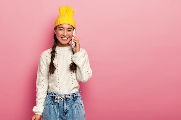 Happy positive mixed race teenage woman enjoys communication via cellphone, wears stylish yellow hat