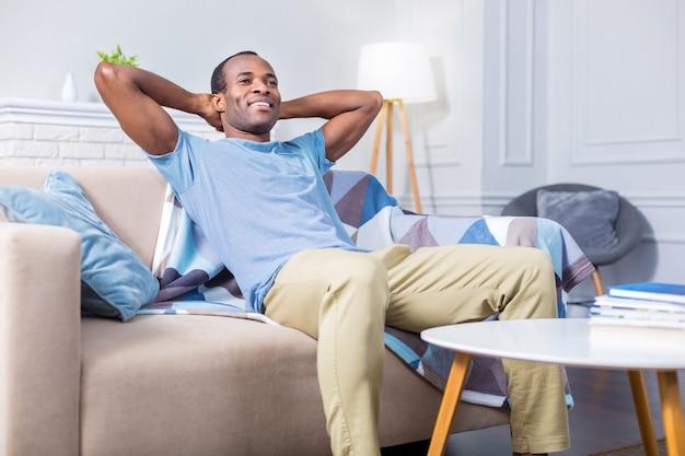 Счастливый позитивный приятный мужчина сидит на диване и улыбается, отдыхая дома