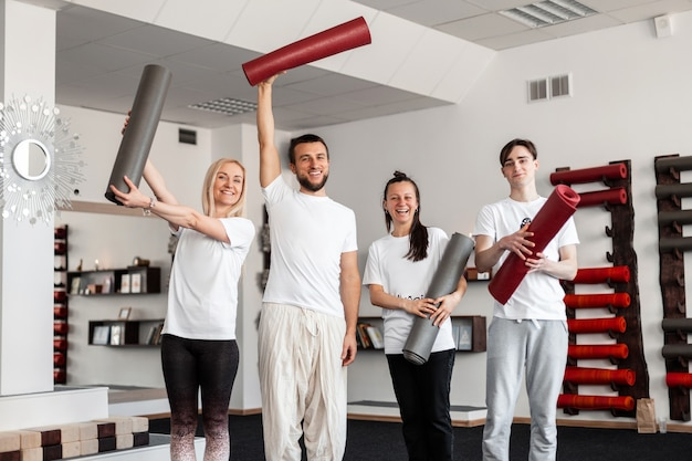 Happy positive people in sportswear is standing with sports mats in the gym. group yoga classes.