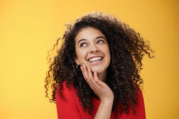 Felice bella giovane donna positiva con i capelli ricci in camicetta rossa che ride sciocco e spensierato mentre guarda compiaciuto nell'angolo in alto a sinistra, toccando il viso, soddisfatto e felice sul muro giallo.