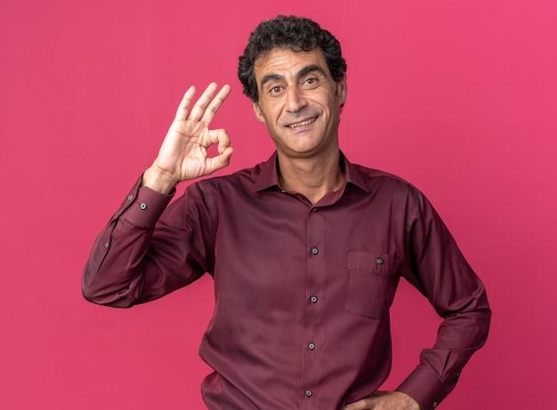 Felice e positivo uomo anziano in camicia viola che guarda la telecamera sorridendo allegramente facendo segno ok in piedi su sfondo rosa