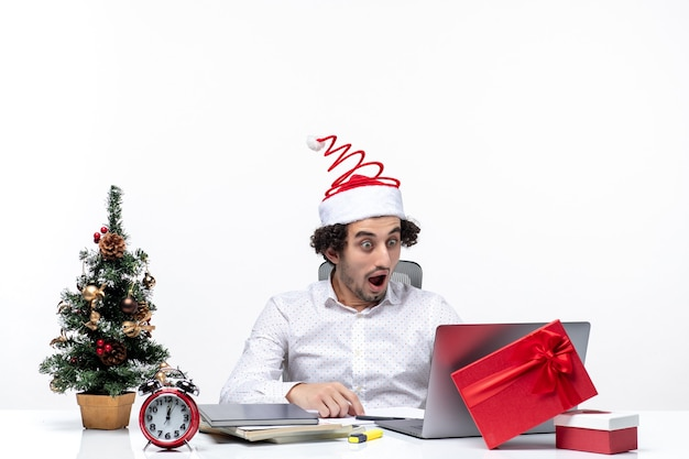 Happy positive shocked young businessman with funny santa claus hat checking his carefully in the office on white background