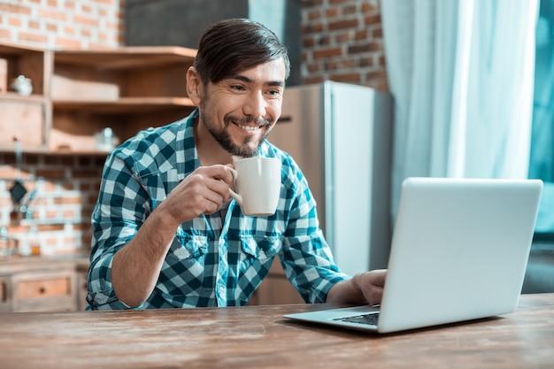 ラップトップの前に座って、自宅で仕事をしながらお茶を飲んで幸せなポジティブスマートな男