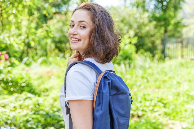 Happy positive student girl with backpack smiling on green park background.