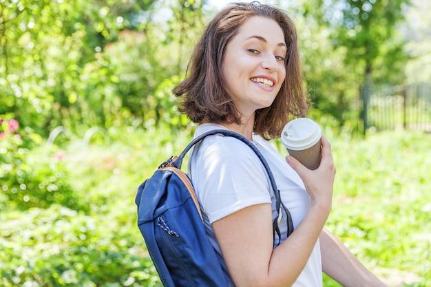 배낭 녹색 공원 배경에 웃 고 행복 긍정적 인 학생 소녀.