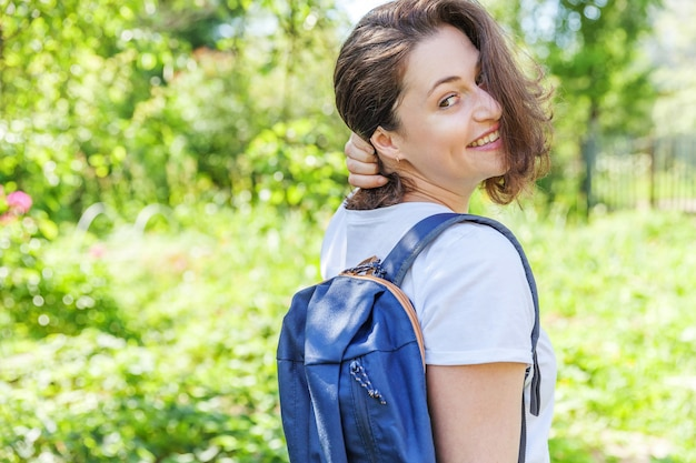녹색 공원 배경에서 웃고 있는 배낭을 메고 행복한 긍정적인 학생 소녀