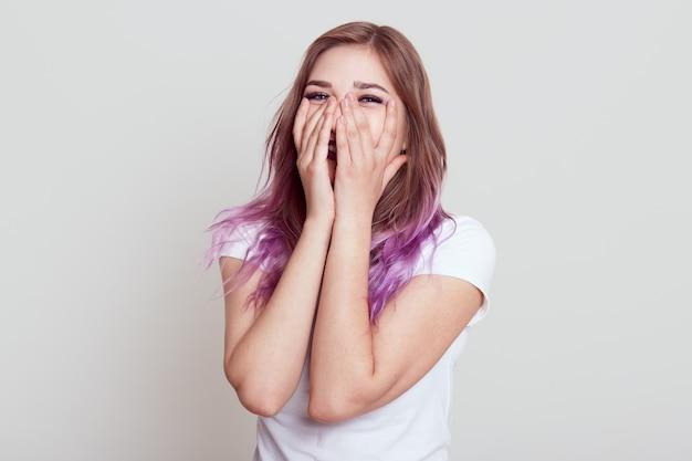 행복하게 웃고, 손바닥으로 얼굴을 덮고, 기쁨을 표현하고, 회색 벽 위에 절연 포즈를 취하는 라일락 머리를 가진 흰색 캐주얼 티셔츠를 입고 행복 긍정적 인 세련된 여성.