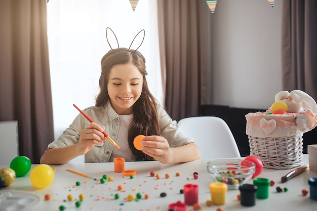 Happy positive teenager painting eggs