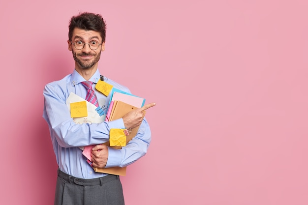Happy positive unshaven man office worker demonstrates results of his research work stuck with stickers holds folders with documents indicates aside on blank space