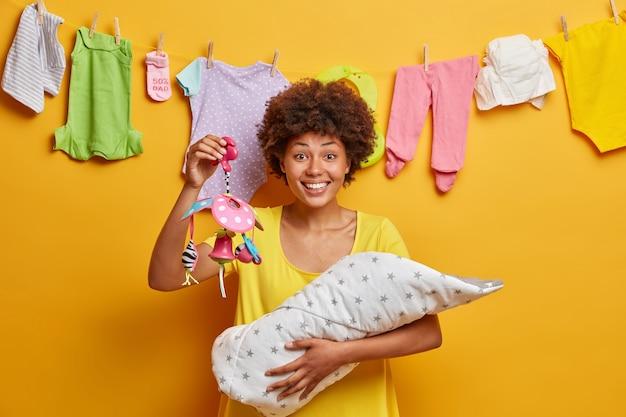 Счастливая позитивная женщина несет ребенка в одеяле и держит мобильный телефон дает новую жизнь дочери, одетой в позы повседневного платья