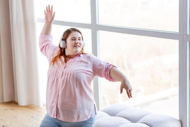 Счастливая позитивная женщина танцует под свою любимую музыку в отличном настроении