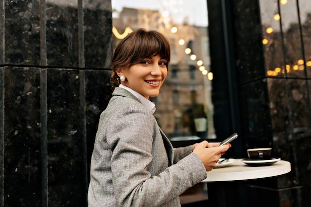 幸せなポジティブな女性は、外のカフェでスマートフォンとカメラでポーズをとって灰色のジャケットを着ています