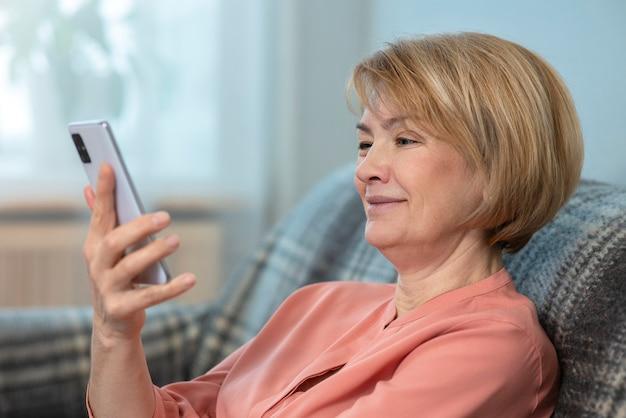 幸せなポジティブな女性、年配のシニア成熟した女性は彼女の携帯電話の画面を見ていると