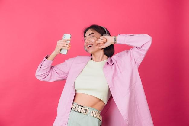 분홍색 빨간 벽에 헤드폰에서 행복 한 긍정적 인 여자