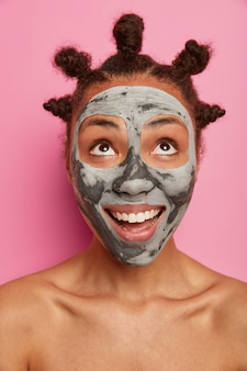 Happy positive woman looks upwards, applies purifying facial mask, removes blackheads, looks curiously upwards, stands shirtless, has well cared body healthy skin combed hair buns poses over rosy wall