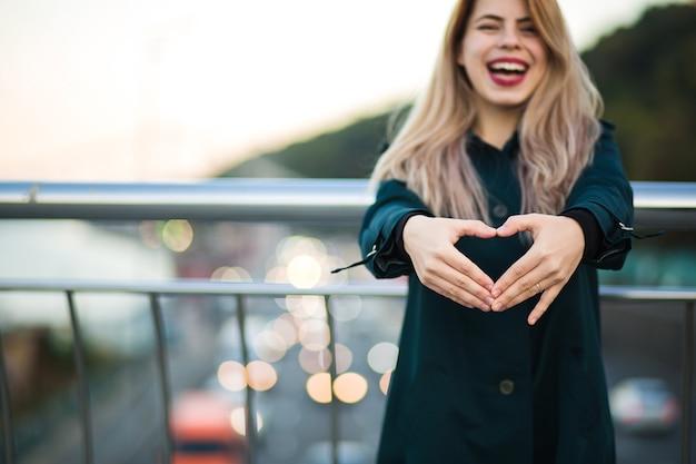 Счастливая положительная женщина, показывающая сердечный жест от ее пальцев. место для текста