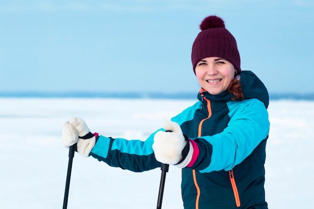 Счастливая позитивная женщина катается на лыжах в зимней теплой одежде и шляпе на открытом воздухе в холодный солнечный день