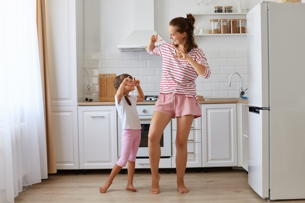 Happy positive woman wearing striped shirt dancing with her daughter at home, making victory gesture moving, looking at each other with happy smile, having fun together in kitchen.