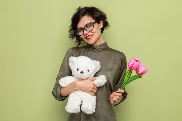 Happy and positive woman with short hair holding bouquet of tulips and teddy bear looking at camera smiling cheerfully celebrating international women's day march 8 standing over green background