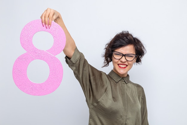 Happy and positive woman with short hair holding number eight made from cardboard looking at camera smiling cheerfully celebrating international women's day march 8 standing over white background