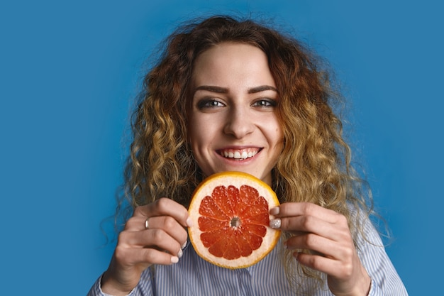 신선한 자몽 조각을 들고 물결 모양의 헤어 스타일을 가진 행복 긍정적 인 젊은 25 세 여자는 마치 수분이 많은 비타민 과일을 제공하는 것처럼 손을 뻗습니다. 건강한 라이프 스타일과 과일주의 개념