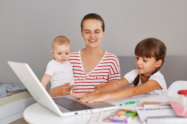 Happy positive young adult mother with baby in hands sitting at table and helps her elder daughter to do home task or helping during lesson, looking smiling at laptop computer.