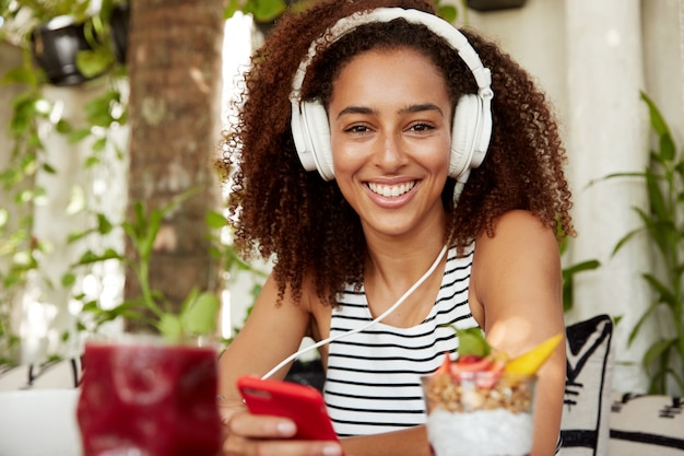 Happy positive young african american female reads message on mobile phone, listens audio with headphones, rests after work in cozy restaurant, enjoys free internet connection. leisure and rest